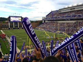 Students cheering on the Dukes at a JMU football game in Bridgeforth Stadium