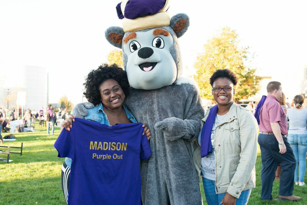 Two JMU students smiles with the Duke Dog at the 2014 Homecoming Purple Out Event.