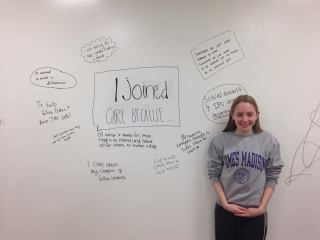 """Trained CARE member Alexandra Weathersby in front of a whiteboard, with the words """"I Joined CARE Because . . .""""at a fall meeting."""