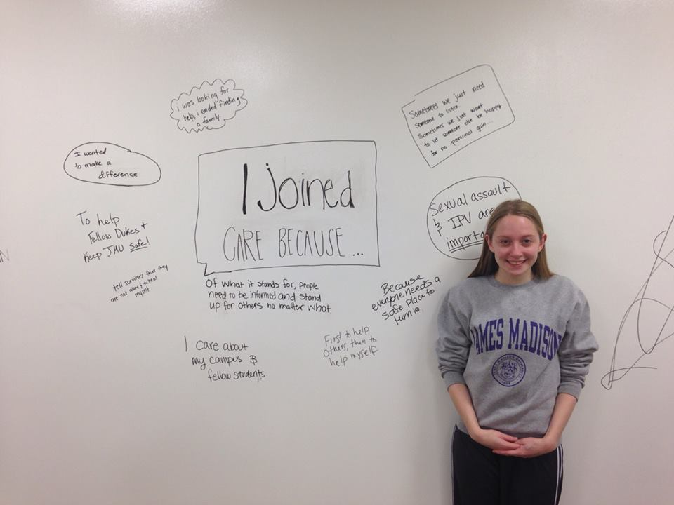 "Trained CARE member Alexandra Weathersby in front of a whiteboard, with the words ""I Joined CARE Because . . .""at a fall meeting."