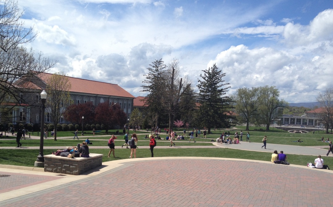 A shot of the quad during a sunny day with students sitting or laying in the grass.