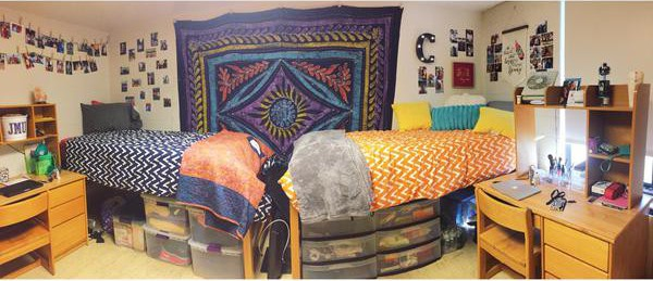 A decorated dorm room with two beds and a tapestry