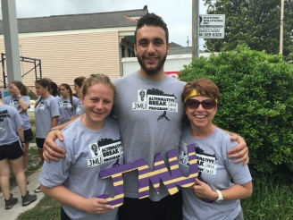 "Two students and a faculty member from JMU smile at the camera while holding a small wooden ""JMU"" sign."