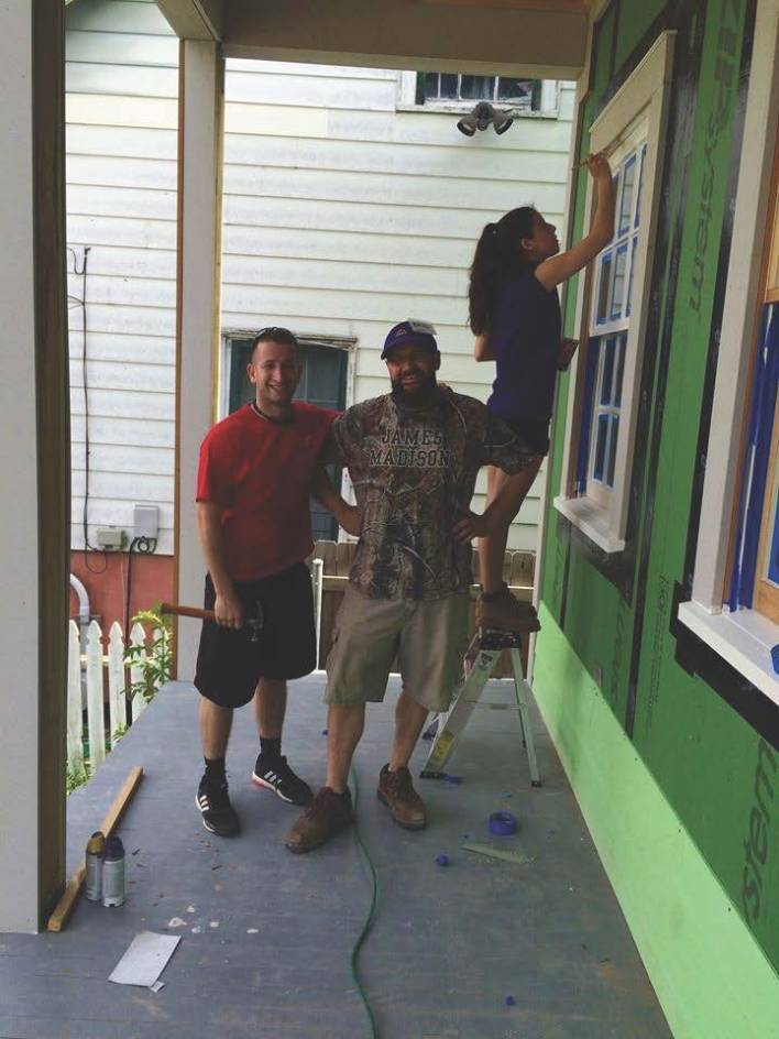Standing on a porch, two volunteers smile at the camera while a third paints the framing a window.