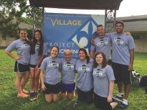 A group of Alternative Break members stand in a group and pose in front of a large sign for the location where they are volunteering.