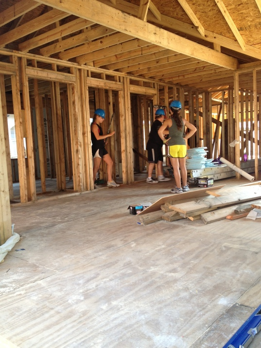 Several APB volunteers work on the framing of a house inside of a construction site.