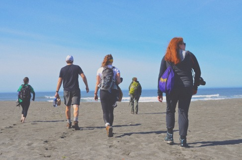Several students carrying backpacks walk with their back to the camera across a beach towards and ocean.