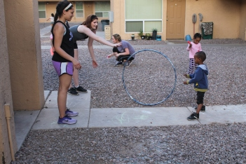 A group of students play with several children in a courtyard.