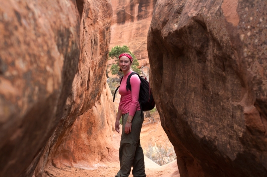 A student in hiking gear stands in between two rock canyon walls.