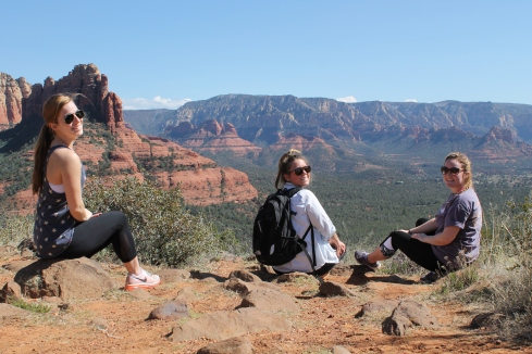 Three students sit on the edge of a canyon and smile at the camera.