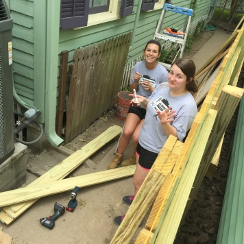 Two JMU students during the 2015 May Break work on the side of a house in the Gulf Coast.