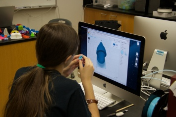 Debbie Trader examines her printed model to compare it to the computer model.
