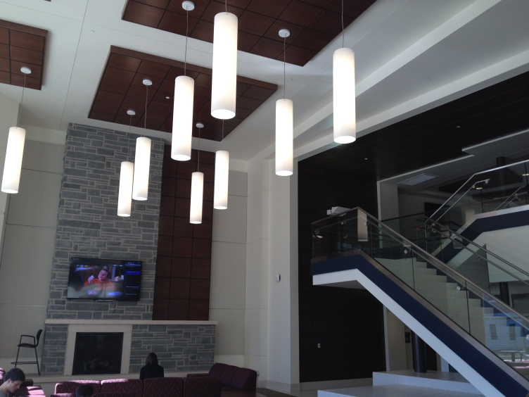 The lobby of the apartments includes large light fixtures and a wide staircase leading to the second floor.