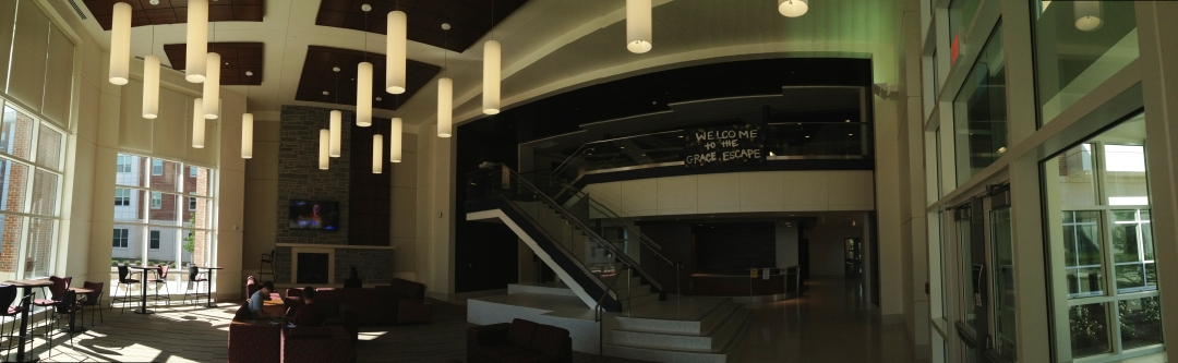The lobby of the Grace Street Apartments, which includes large light fixtures and flat screens TV.
