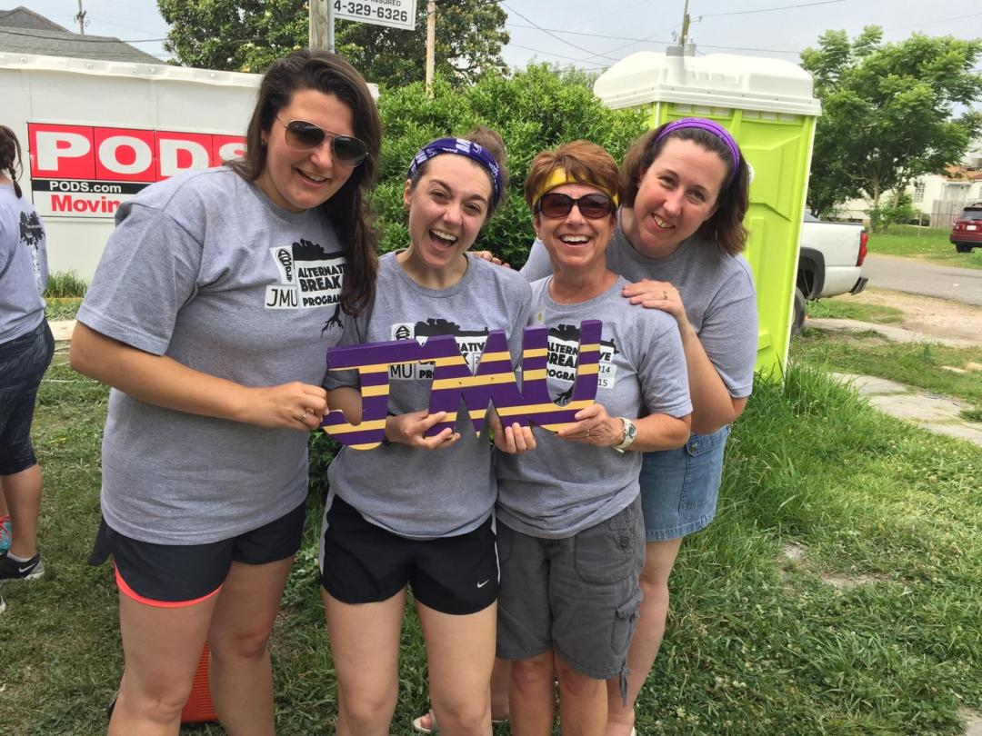 A group of Site Leaders during the 2015 May Break hold a JMU sign and smile at the camera.
