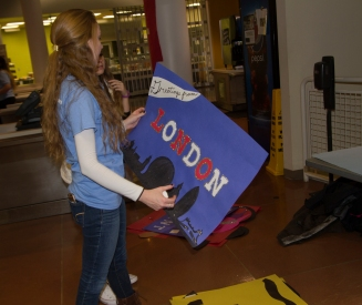 "A committee member holds a ""London"" sign decorated with glitter."